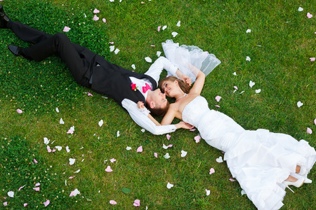 Happy wedding couple lying on green grass at the summer time