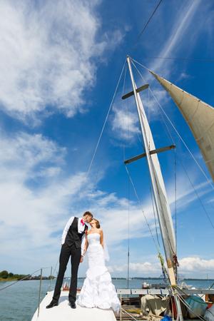 parejas romanticas: Pares de la boda que se besan en un yate en el horario de verano