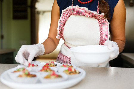 candied fruits: Young woman puts candied fruits on the cakes at the kitchen