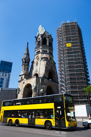 kaiser: Berlin, Germany - July 07 2015: Yellow touristic bus on the road against Church of the Kaiser Wilhelm at summer time