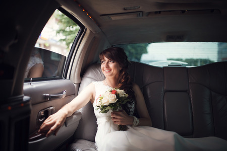 Smiling bride looking out the window of the car