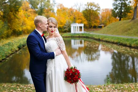 water fall: Wedding couple hugging by the lake in the fall Stock Photo