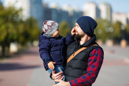 父と息子の秋の時に街を歩いて 写真素材