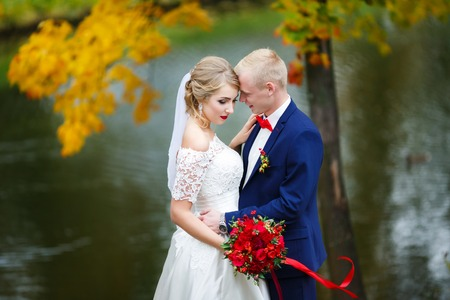 Wedding couple hugging by the lake in the fall Stock Photo