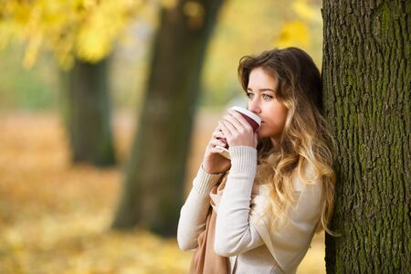 checkered scarf: Teenage girl with cup of coffee in a forest at autumn time Stock Photo