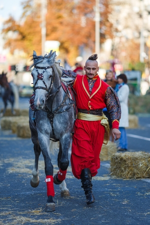 cossacks: Kiyv, Ukraine - October 10 2015: The show of riding, ukrainian cossacks dressed in traditional costumes show their skills of riding on the central street Khreschatic in autumn Editorial