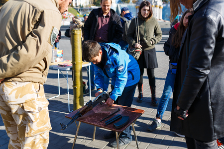 civilians: Kiyv, Ukraine - October 10 2015: A boy is learning the structure of the Kalashnikov gun during the exhibition of arms as an evidence of Russian Armys aggression upon Ukraine at Donbass, autumn time. Editorial