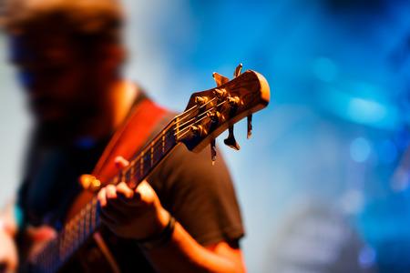 bass guitar: Man playing bass guitar during a concert