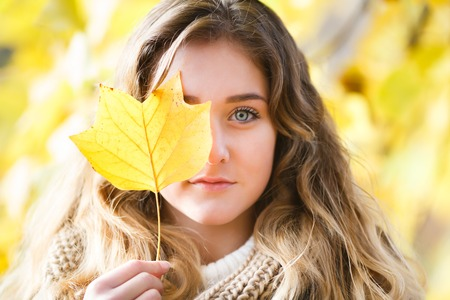 Portrait of a girl covering one eye leaf in fall