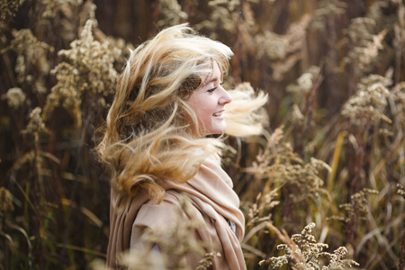 underbrush: Young girl running through the underbrush with wind in her hair, autumn time