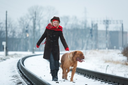 bordeauxdog: Teenage girl with a Bordeauxdog walking along the railroad at winter time