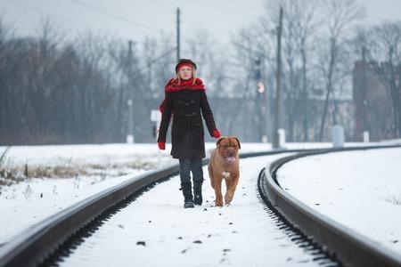 Tiener met een Bordeauxdog die langs de spoorweg in de wintertijd loopt Stockfoto