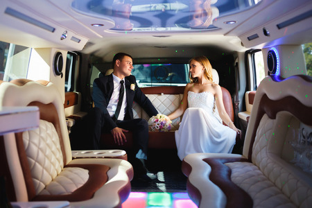 Happy bride and groom sitting in limousine Stock Photo