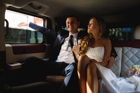 limousine: Happy bride and groom sitting in limousine Stock Photo