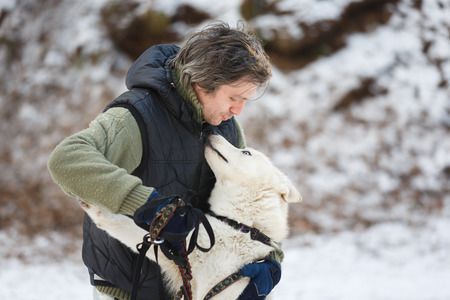 alaskian: Man embracing with husky in winter forest Stock Photo
