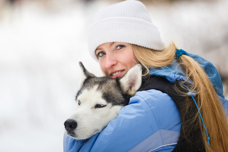 alaskian: Young woman with husky dog in winter
