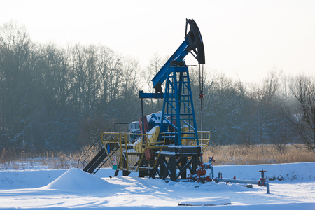 roughneck: Oil derricks on snowy field at winter time