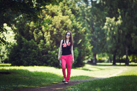 young adult woman: Young woman walking in a park at summer time Stock Photo