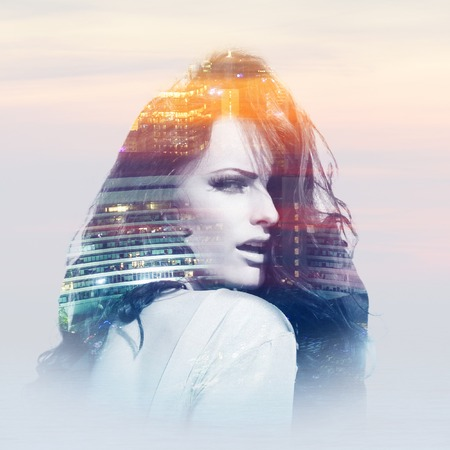 Double exposure of young woman with buildings of metropolis Stock Photo