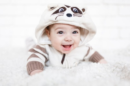 0 6: Little boy dressed in raccoon suit and lying on a white soft rug in studio