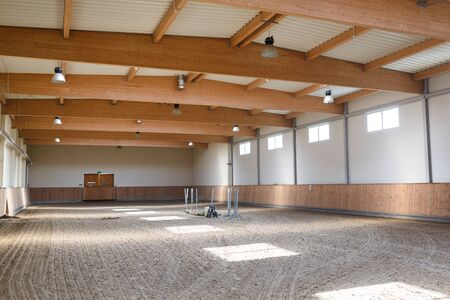 arena: The empty bright manege for equestrian training indoor