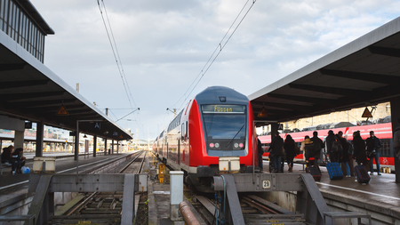 railroad station platform: Munich, Germany - January 06 2016: Tourists go to the train traveling to Fussen on the platform of the Railroad Station in Munich