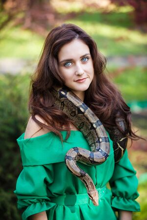 garden green: Portrait of the attractive teenage girl with snake in a garden Stock Photo
