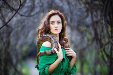 Portrait of the attractive teenage girl with snake in a garden Stock Photo