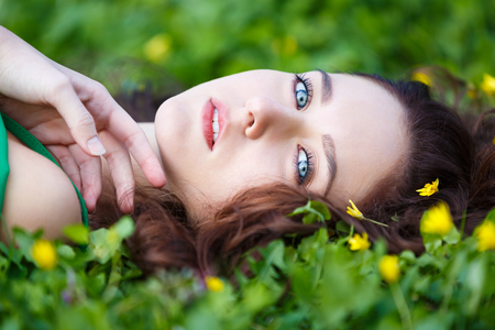 Attractive woman lying in the green grass