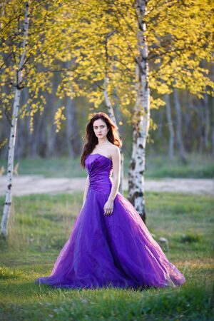 evening gown: Attractive girl dressed evening gown under the birch