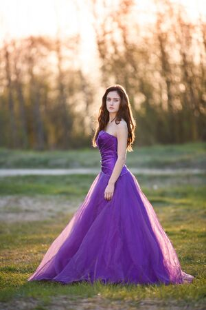 evening gown: Attractive girl dressed evening gown at sunset