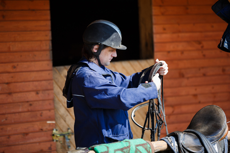 horse harness: Rider holding a horse harness before training in the stables Stock Photo