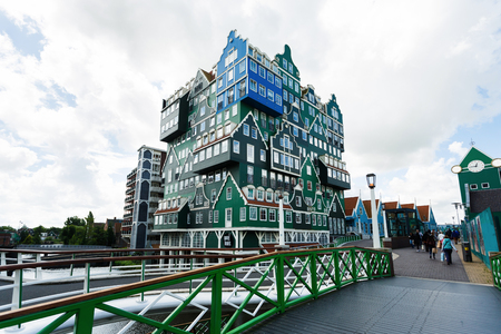 Zaandam, Netherlands - July 02 2016: Some people are walking on the bridge nearby the Inntel hotel, the famous building of traditional architecture in Dutch region