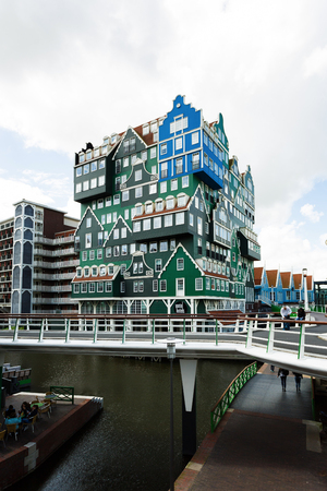 zaandam: Zaandam, Netherlands - July 02 2016: Some people are walking on the bridge nearby the Inntel hotel, the famous building of traditional architecture in Dutch region