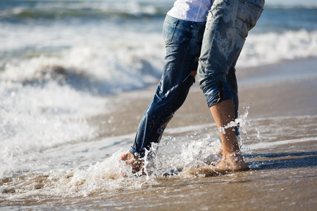 wet jeans: Legs of couple are standing on the beach, summer time Stock Photo