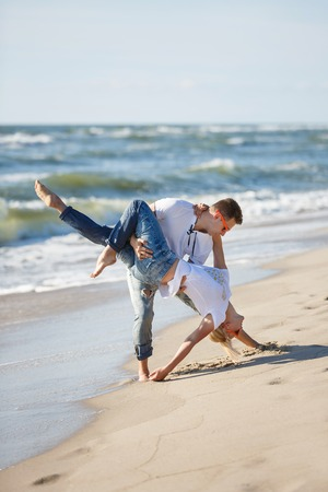 Cheerful couple are making acrobatic dance on the beach, summer time Stock Photo