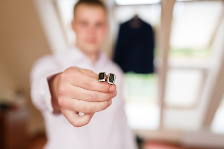 Man puts the cufflinks in a room
