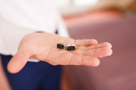 cuff link: Man puts the cufflinks in a room