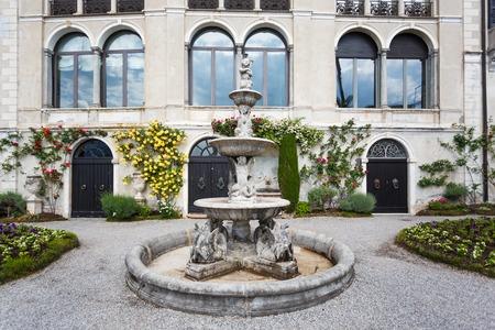 Varenna, Italy - May 06 2016: The fountain in a garden of Villa Monastero, spring time