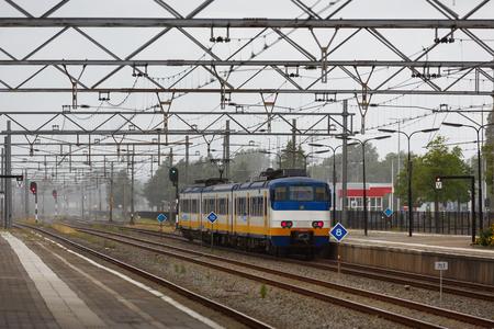 zaandam: The moving train on the background of the urban landscape in Zaandam Stock Photo