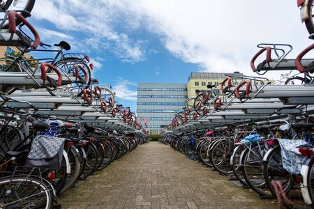 Zaandam, Netherlands - July 02 2016: Bicycle parking on the background of the traditional dutch buildings, summer time Editorial