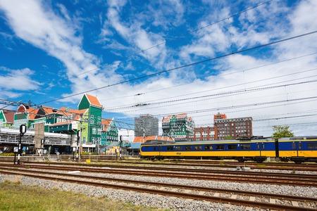 zaandam: Zaandam, Netherlands - July 02 2016: The train arrives at the station on the background of the urban landscape, summer time