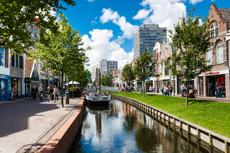 build up: Zaandam, Netherlands - July 02 2016: Some people are walking on a central street, build up with traditional Dutch houses Editorial