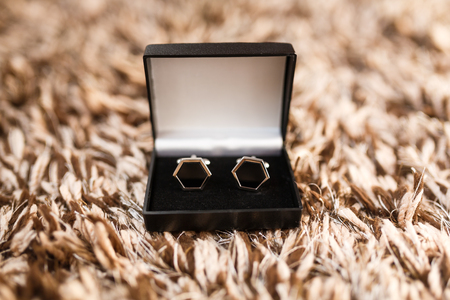 cuff link: The cufflinks in a box on a wool surface Stock Photo