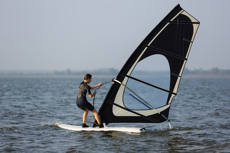 sailboard: Young windsurfer training in the summer sea