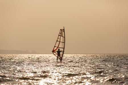 sailboard: Exercising windsurfer in a sea at sunset