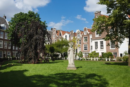Amsterdam, Netherlands - July 03 2016: The monument in courtyard of Begijnhof Chapel, sunny day Editorial