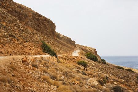 Bad mountain road along the high rocky shore leading to the beach Balos