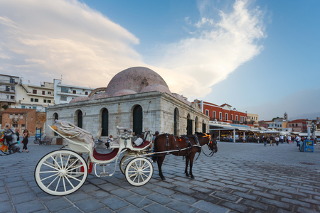 expects: Chania, Greece - October 11 2016: Horse carriage expects tourists near the Mosque of the Janissaries in old town of Chania Editorial