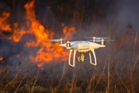 Die Drohne fliegt vor dem Hintergrund eines Frühlingswaldbrandes Standard-Bild - 76034007